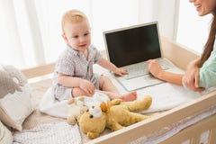 使用有她的男婴的愉快的母亲膝上型计算机 免版税图库摄影