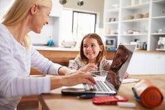 使用有她的年轻女儿的母亲便携式计算机 免版税库存照片