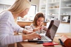 使用有她的年轻女儿的母亲便携式计算机 免版税图库摄影