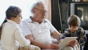 使用有孙的一个年长人一台片剂计算机 股票录像