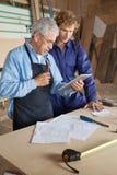 使用有工友的木匠数字式片剂 免版税库存照片