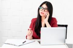 使用有微笑的面孔的亚裔女商人智能手机在offic 免版税库存照片