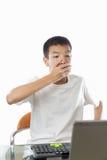 使用有惊奇的面孔的亚裔少年计算机 免版税库存照片