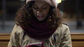 使用有手套的可爱的快乐的混合的族种女孩智能手机,有风晚上 股票录像