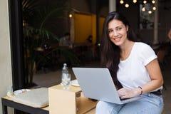 使用有拷贝空白区的一个微笑的行家女孩的画象便携式计算机为您的正文消息或给内容做广告 库存图片