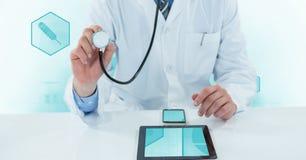 使用有数字式片剂和手机的医生的中央部位听诊器在书桌上 库存照片