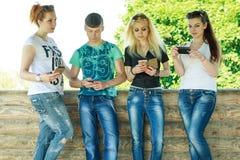 使用有无兴趣的小组年轻行家朋友巧妙的电话在彼此 库存图片