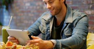 使用有杯的人数字式片剂在桌上的汁液 股票录像