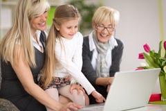 使用有母亲和祖母的小女孩膝上型计算机 免版税库存照片