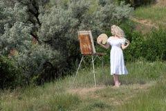 使用有油漆的,一个调色板美丽的女孩画一张图片在公园 画架和帆布与图片 库存照片