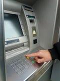 使用有现金卡的, ATM机器供以人员` s 键入在ATM/bank机器键盘的手特写镜头PIN/pass代码 免版税库存图片