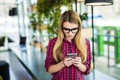 使用有现代办公楼的企业家妇女一个巧妙的电话在背景 库存图片