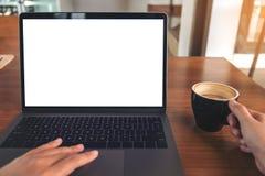 使用有空白的白色屏幕的妇女的大模型图象膝上型计算机,当喝在木桌上时的咖啡 免版税图库摄影