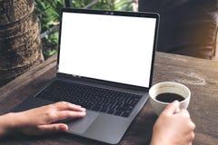 使用有空白的白色屏幕的妇女的大模型图象膝上型计算机,当喝在木桌上时的咖啡 库存照片
