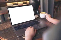 使用有空白的白色桌面屏幕的女实业家膝上型计算机,当喝在木桌上的热的咖啡在咖啡馆时 免版税库存图片