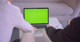 使用有绿色屏幕的两个商人特写镜头后面视图画象膝上型计算机和握手协议在办公室 股票视频