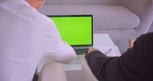 使用有绿色屏幕的两个商人特写镜头后面视图画象膝上型计算机和握手在办公室户内 影视素材
