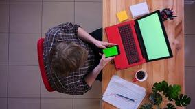 使用有绿色屏幕的年轻白种人商人特写镜头顶面射击电话在膝上型计算机前面用咖啡 股票视频