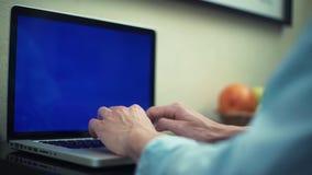 使用有绿色屏幕的,膝上型计算机供以人员键入的消息 在家工作的自由职业者 影视素材