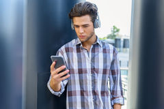 使用有耳机的严肃的人电话 免版税库存图片