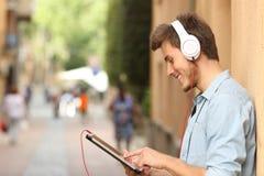 使用有耳机的人一种片剂在街道上 图库摄影