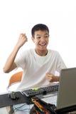 使用有胜利姿态的亚裔少年计算机 免版税库存照片