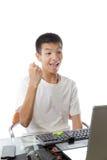 使用有胜利姿态的亚裔少年计算机 免版税图库摄影