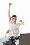 使用有胜利姿态的亚裔少年计算机 库存图片