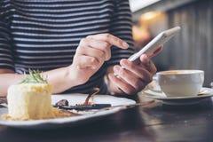 使用有蛋糕和咖啡杯的妇女巧妙的电话在木桌上 库存图片