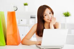 使用有袋子的愉快的年轻亚裔妇女一台膝上型计算机 图库摄影
