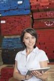 使用有被堆积的木板条的一名可爱的女实业家的画象片剂个人计算机在背景 免版税库存照片