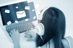 使用有送电子邮件顶头电话的美丽的亚裔少妇一个便携式计算机键盘  图库摄影