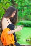 使用有绿叶的美丽的两种人种的青少年的女孩手机在ba 图库摄影