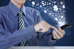 使用有货币符的企业家手机 库存图片