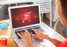 使用有购物台车象的人膝上型计算机 图库摄影