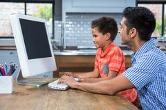 使用有他的儿子的微笑的父亲计算机 免版税库存图片