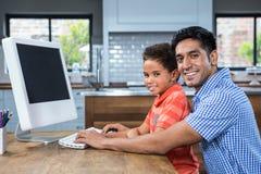 使用有他的儿子的微笑的父亲计算机 免版税库存照片
