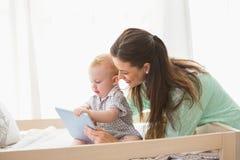 使用有他的男婴的愉快的母亲片剂 库存图片