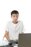使用有滑稽的面孔的亚裔少年计算机 免版税库存图片