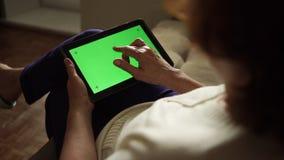 使用有绿色屏幕的,后面看法的年迈的妇女一台数字式片剂个人计算机 股票视频