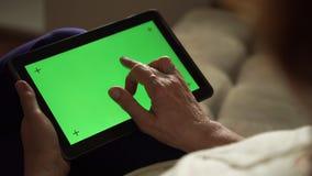 使用有绿色屏幕的,后面看法的年长妇女一台数字式片剂个人计算机 影视素材