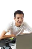 使用有兴高采烈的面孔的亚裔少年计算机 库存图片