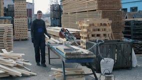 使用木切割机的工业年轻木匠工作者 人切开木板条 影视素材
