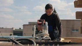 使用木切割机的工业年轻木匠工作者 人切开木板条 股票视频