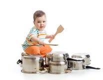 使用木匙子的小男孩猛击平底锅drumset 免版税库存照片