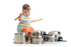 使用木匙子的男婴猛击平底锅drumset 免版税库存照片