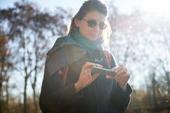 使用未来派iPhone室外太阳火光的妇女 库存图片
