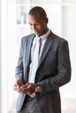 使用机动性的一个年轻非裔美国人的商人的画象 免版税库存图片