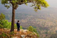 使用机动性的旅客在峭壁自然背景边缘 免版税库存图片