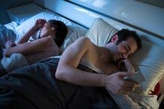 使用机动性的狡猾的男朋友在床 免版税库存照片